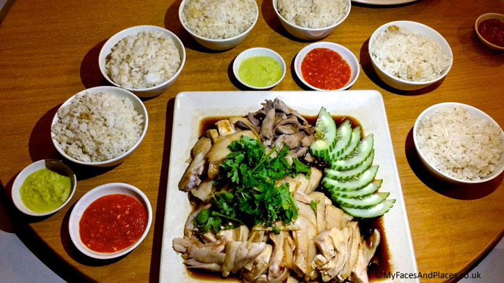 Hainanese Chicken Rice served with condiments of minced ginger and chilli sauce in Hainanese Delights.