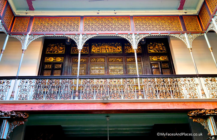 An interior view of the Blue Mansion in Goerge Town, Penang. Note the ornate cast iron baluster with the intricate Chinese wooden motifs in the background.